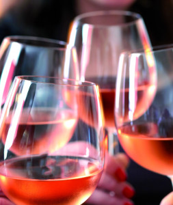 Closeup of four glasses with wine being clinked together during a toast at a celebration