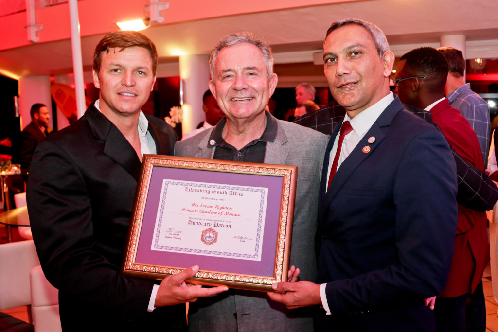 Dylan Tommy, President of Lifesaving South Africa, presenting official patronage to Gareth Wittstock on behalf of HSH Princess Charlene, with Gavin Varejes, President of the Princess Charlene of Monaco Foundation South Africa.