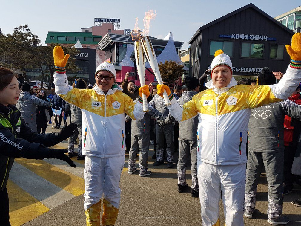 Prince Albert passes the Olympic torch to the South Korean actor Eui-sung Kim. Photo: JO Pyeongchang